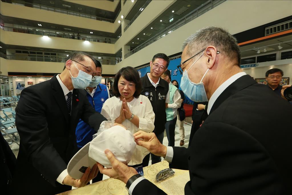 顏博文執行長向黃敏惠市長介紹慈濟因應賑災需求研發的慈悲科技,圖為太陽能環保燈帽。(圖為慈濟基金會提供)